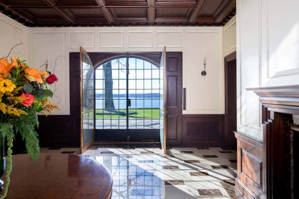 Upon entry of the house, you are welcomed by this foyer that has has a large double door that matches the wooden coffered ceiling, the wainscoting and the round table by the fireplace. Image courtesy of Toptenrealestatedeals.com.