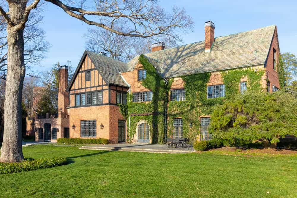 This is a look at the front of the mansion that has tall chimneys, multiple windows and an earthy tone to its brick exterior walls complemented by the creeping vines and lush landscaping. Image courtesy of Toptenrealestatedeals.com.