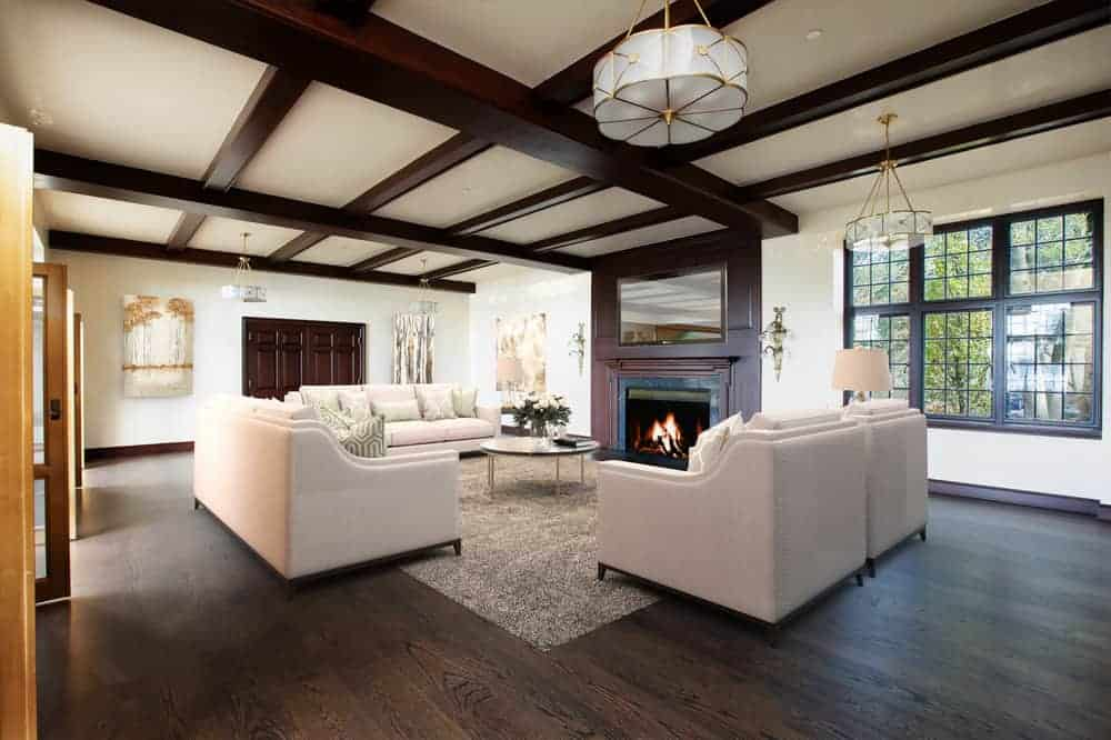 The formal living room has a dark hardwood flooring that matches the beams of the beige ceiling and the mantel of the fireplace across from the beige sofas and coffee table. Image courtesy of Toptenrealestatedeals.com.