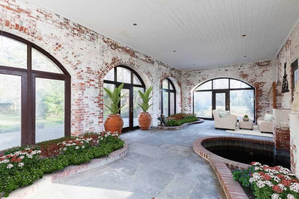 This is a bright and spacious patio with arches of glass, colorful planters of flowering shrubs, potted plants and even a water feature by the sitting area of beige sofas on the far side. Image courtesy of Toptenrealestatedeals.com.