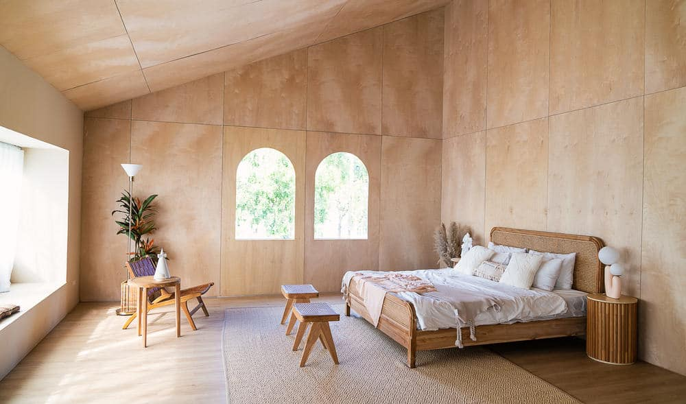 This is a look at a cottage bedroom with a rustic minimalist style. It has a consistent wooden tone to its walls, arched ceiling, bed and bedside tables.