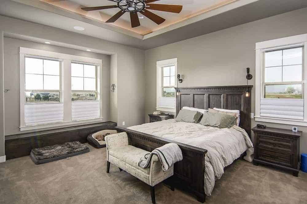 This bedroom is dominated by a alrge dark wooden bed topped with a tray ceiling that has a large ceiling fan over the cushioned bench at the foot of the bed.