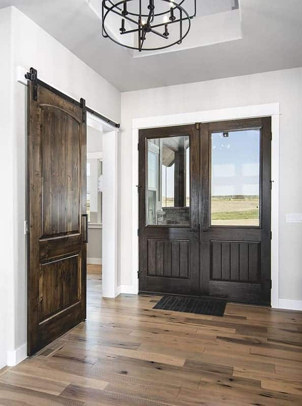 This is a simple foyer with dark double doors complemented by the glass panels. This matches well with the dark hardwood flooring and the wooden sliding door on the side.
