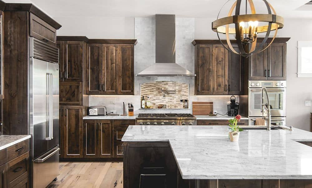 This is a close look at the kitchen that has a large T-shaped kitchen island with cabinets that match those lining the walls contrasted by the white walls and ceiling.