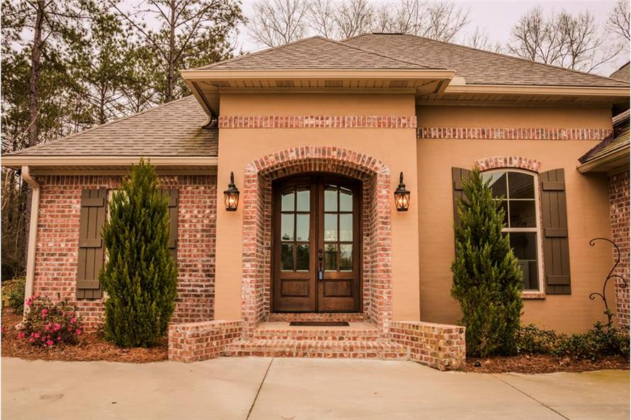 A closer look at the arched entry with a french door, brick stoop, and outdoor sconces.