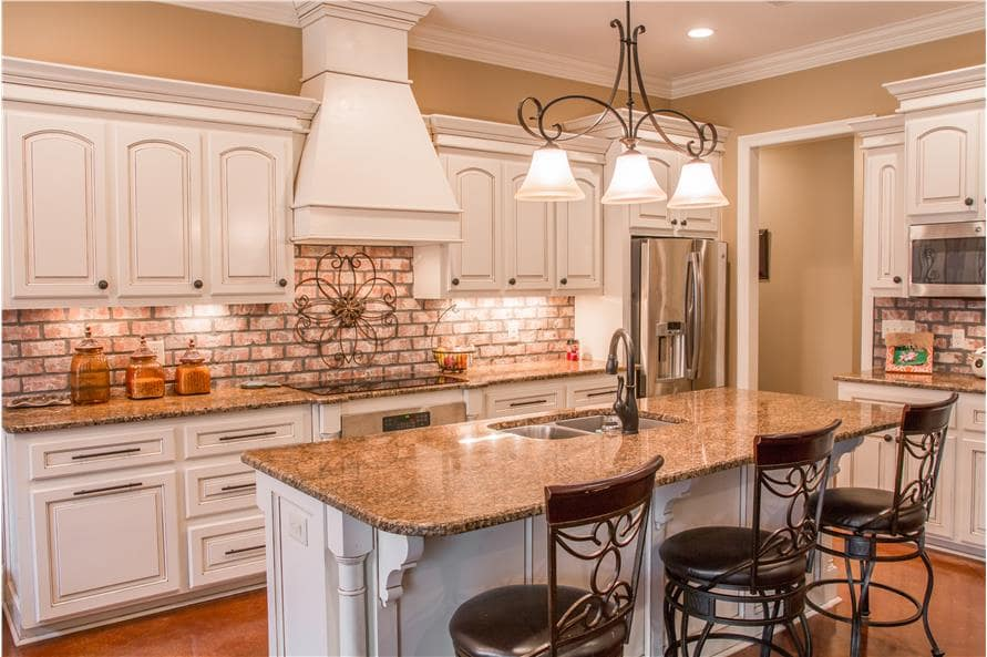 The kitchen is equipped with white cabinetry, a brick backsplash, stainless steel cabinetry, and a breakfast island fitted with a double bowl sink.