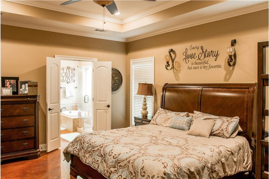 Primary bedroom with wooden furnishings, a tray ceiling, and a double door that opens to the primary bath.