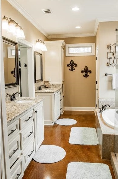 The primary bathroom offers his and her vanities and a deep soaking tub complemented with white rugs.