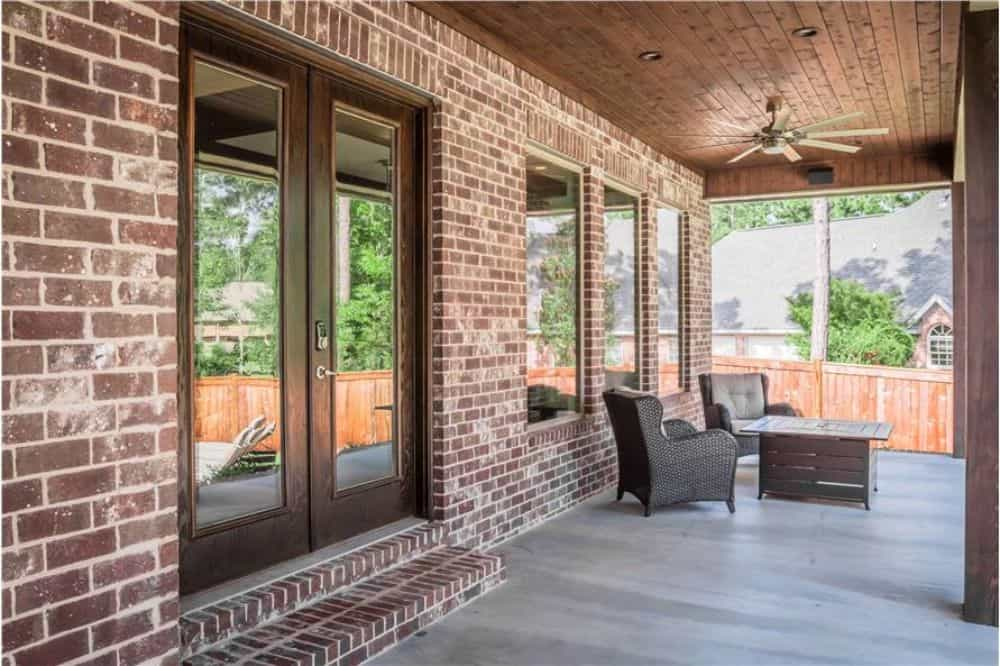 The covered porch has wicker armchairs, a wooden table, and a ceiling fan.
