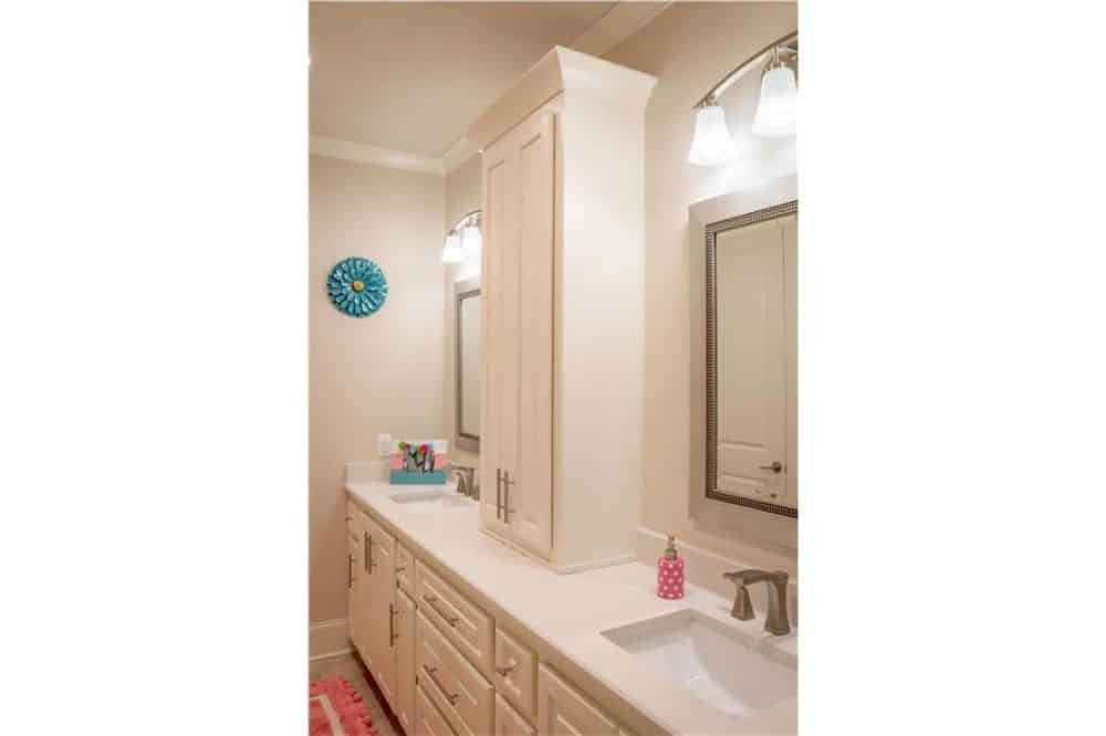 Primary bathroom with double sink vanity topped with a white cabinet and framed mirrors.