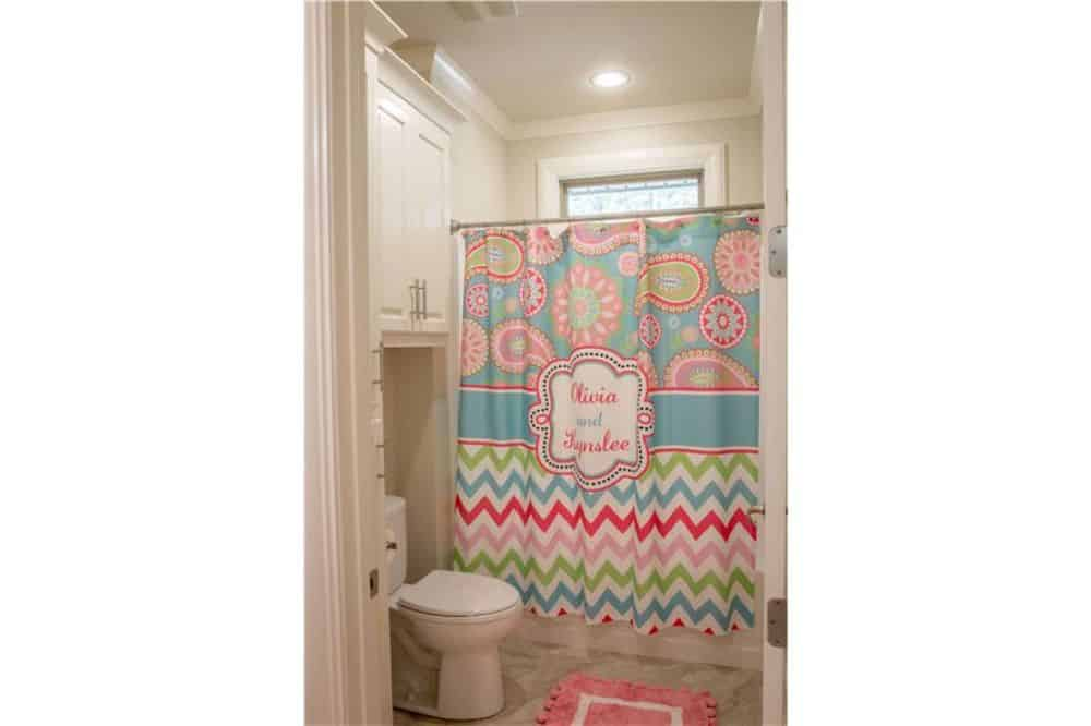 Bathroom with a toilet and a shower area enclosed in a colorful patterned shower curtain.