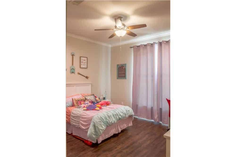 This bedroom has white furnishings, hardwood flooring, and a large window dressed in sheer curtains.