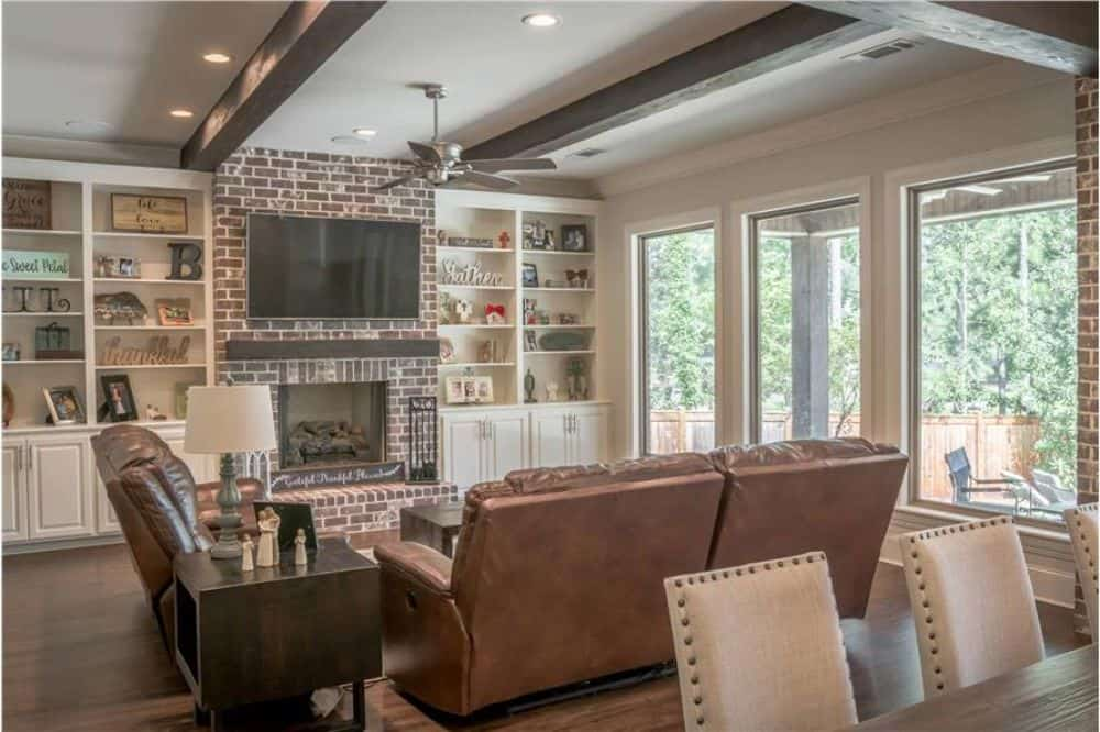 Living room with a beamed ceiling, leather seats, white built-ins, and a brick fireplace topped with a TV.