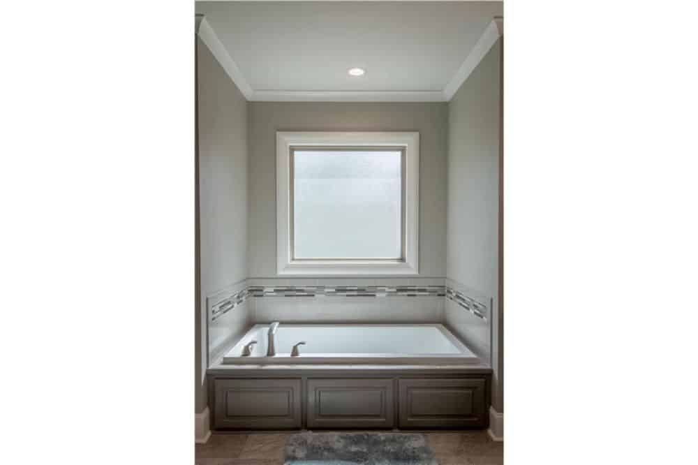 The bathroom includes a drop-in bathtub placed under the picture window.