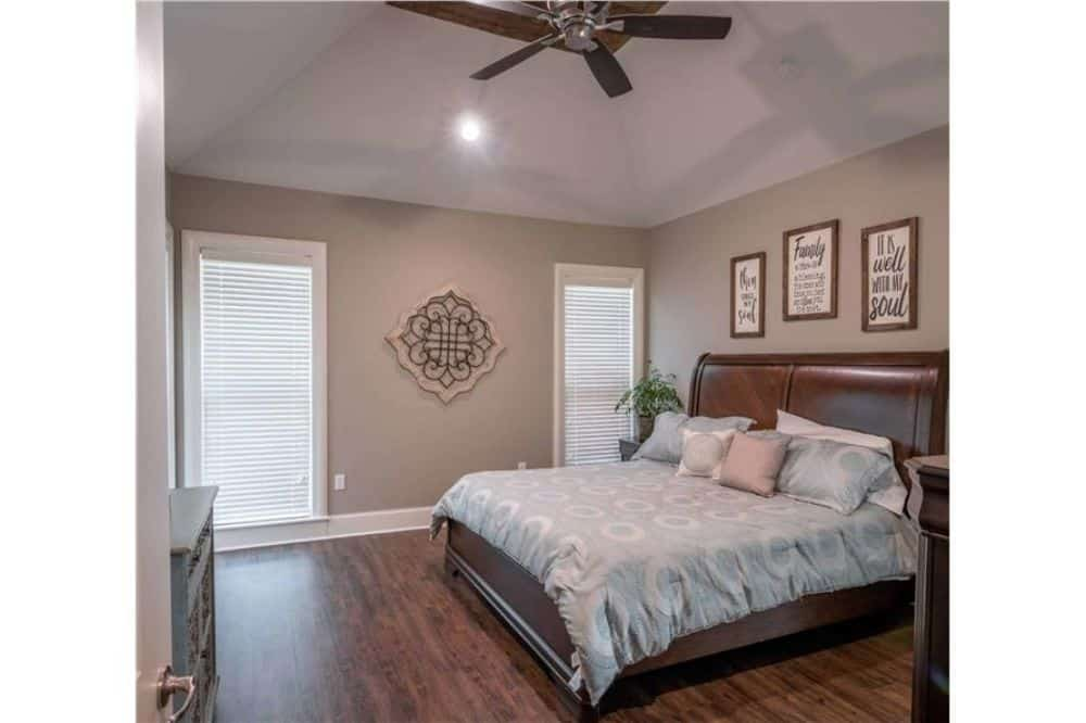 Primary bedroom with a coved ceiling, hardwood flooring, and gray walls adorned with various artworks.