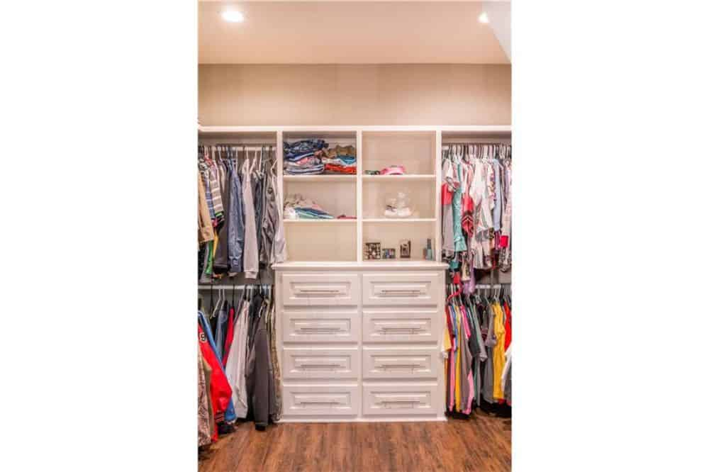 Walk-in closet with white built-in shelves and drawers over the hardwood flooring.