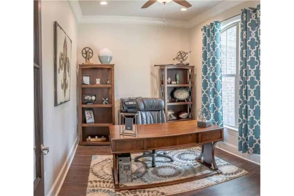 Home office with a wooden desk, leather swivel chair, and a couple of wooden shelving units.