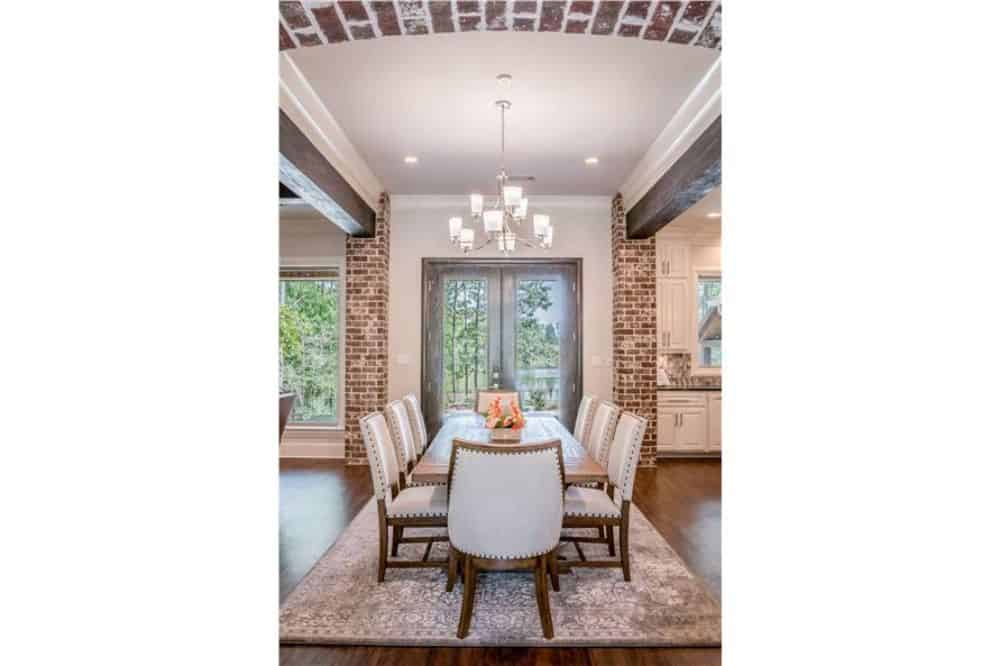 The dining room offers leather upholstered chairs, a rectangular dining table, and a french door that leads to the rear porch.