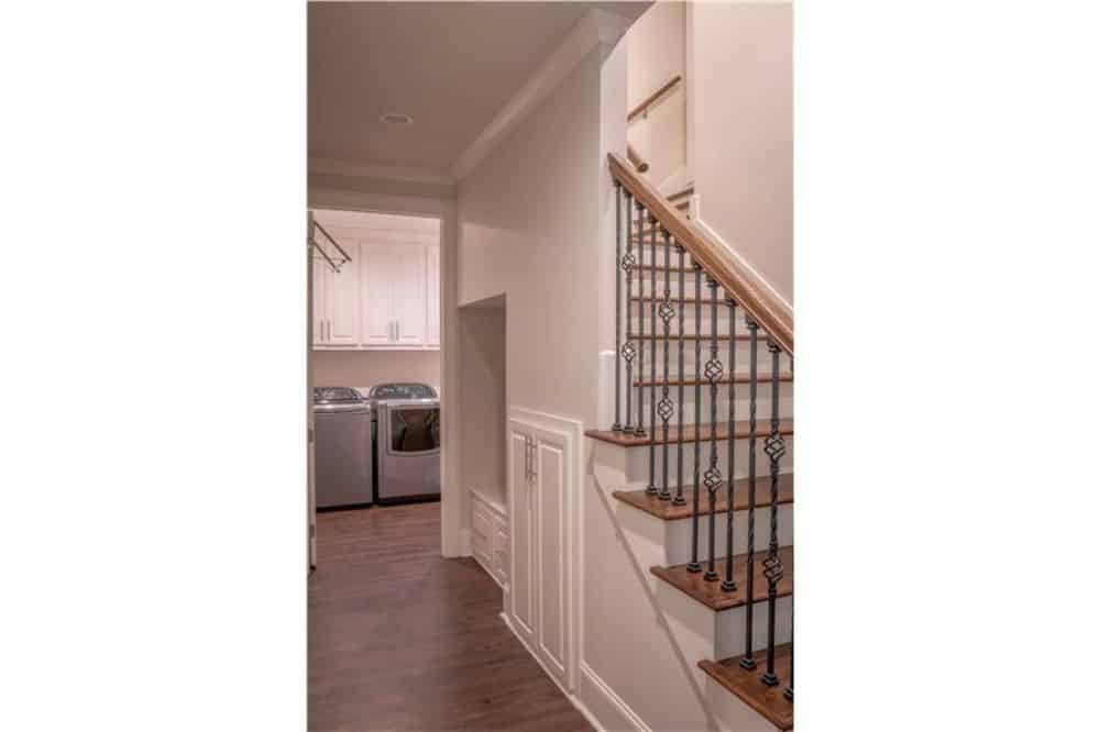 Hallway leading to the laundry room and a staircase that leads to the bonus room.