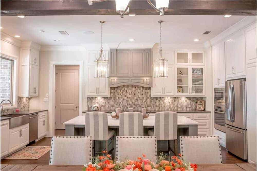 The kitchen is equipped with stainless steel appliances, white cabinetry, a farmhouse sink, and a breakfast island.