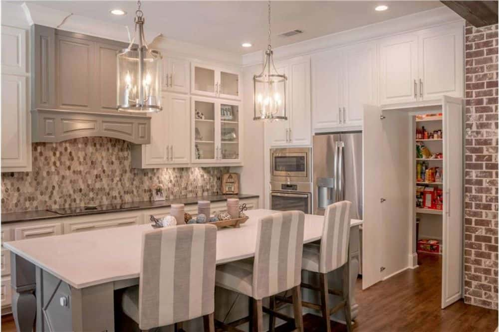 Double white doors next to the fridge reveal the walk-in pantry.