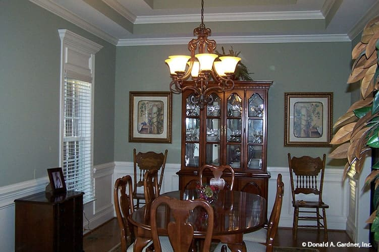 Formal dining room with a tray ceiling, wooden furnishings, and gray walls adorned with white wainscoting and framed artworks.