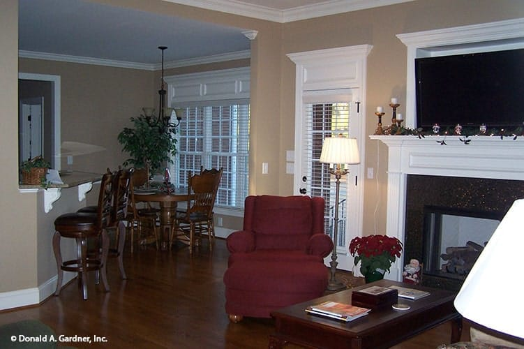 An open layout view showing the living room, dining area, and kitchen with an eating bar.