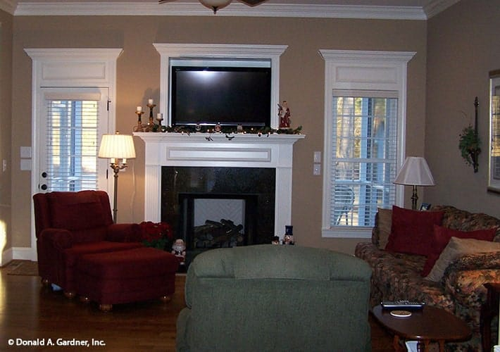The living room offers multi-colored seats, a fireplace, and a wall-mounted TV.