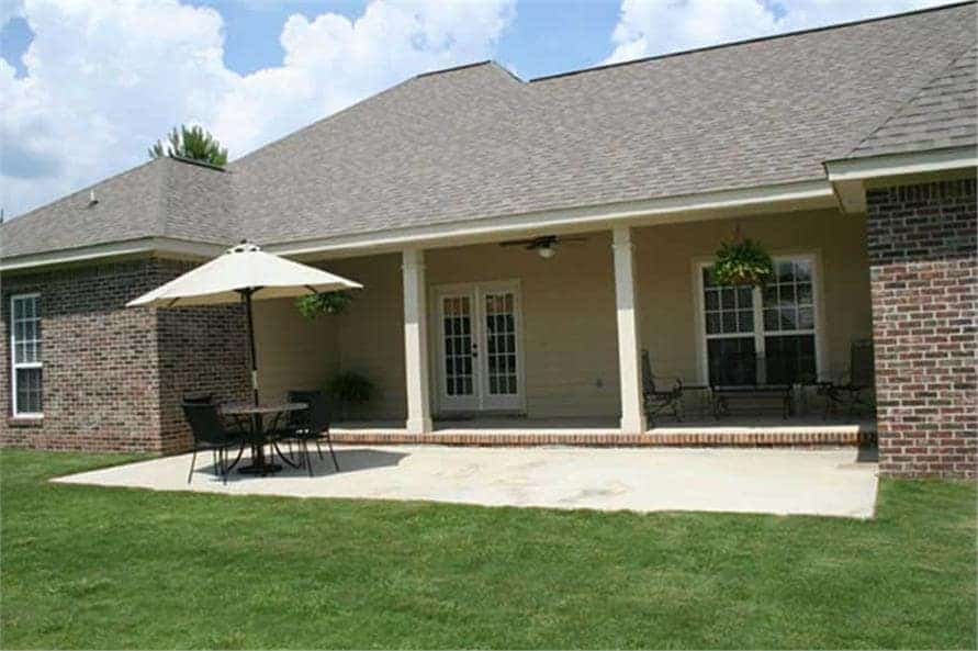 Rear covered porch with metal seats and white columns. It spans onto an airy patio with concrete flooring.