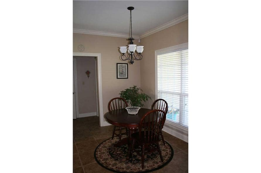 Breakfast nook with a wrought iron chandelier and a round dining set sitting on a round area rug.