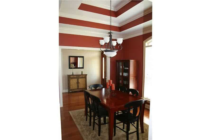 The dining room has dark wood furnishings, red walls, and a stunning step ceiling adorned with an ornate chandelier.