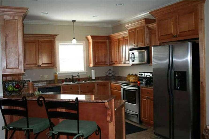 The kitchen is equipped with stainless steel appliances, wooden cabinetry, and a raised eating bar.