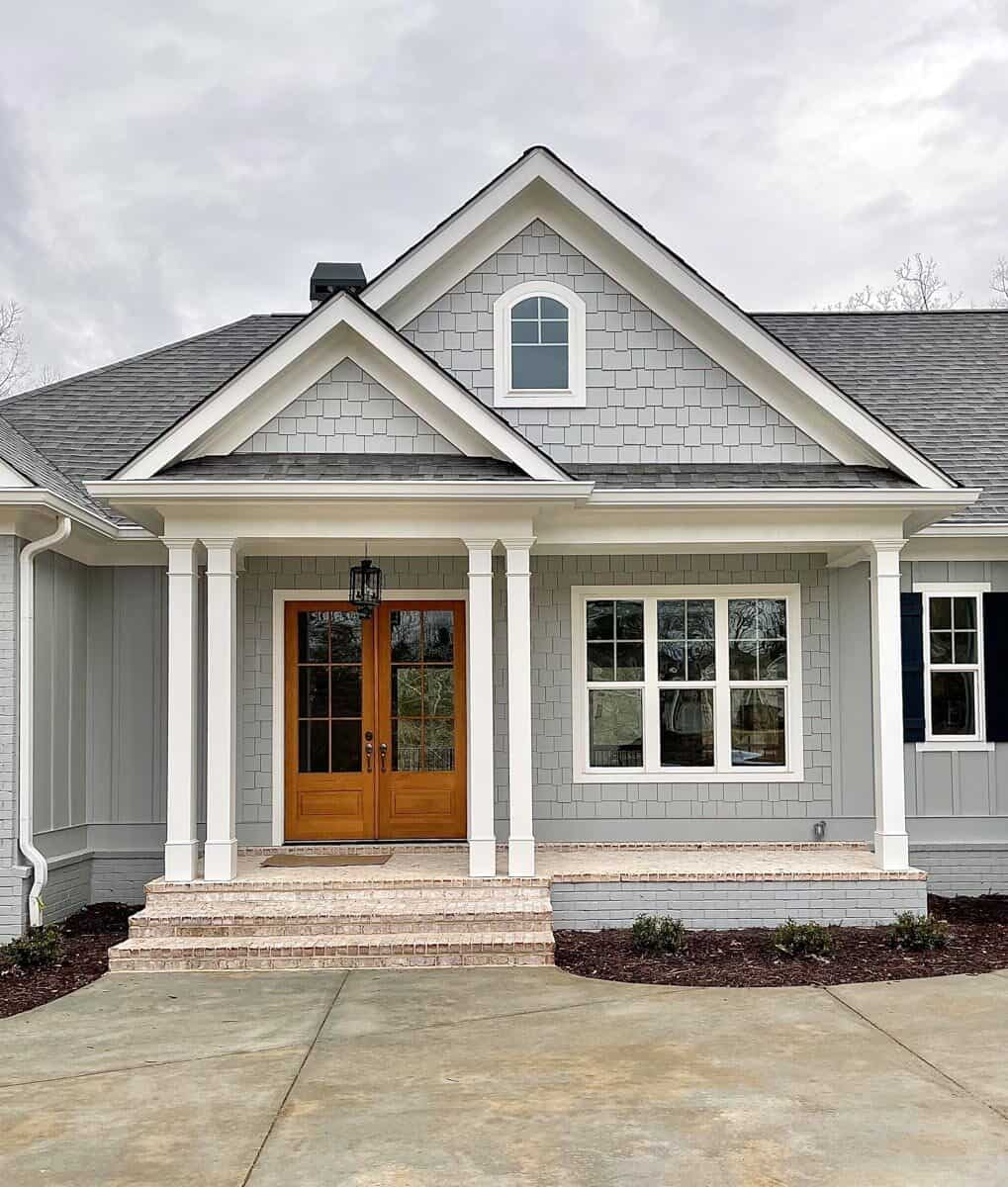 Entry porch with a brick stoop, double columns, and a wooden french door.