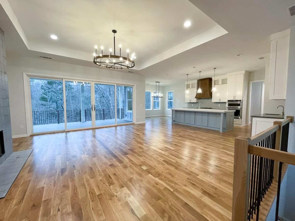 The living space features a tray ceiling and glass sliding doors that open to a covered porch.