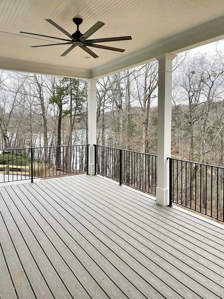 Covered porch with wide plank flooring, white posts, and wrought iron railings that match the ceiling fan.
