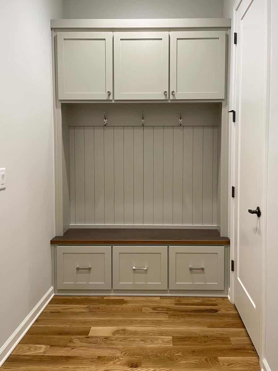 Mudroom with gray cabinets, a built-in bench, and coat hooks.