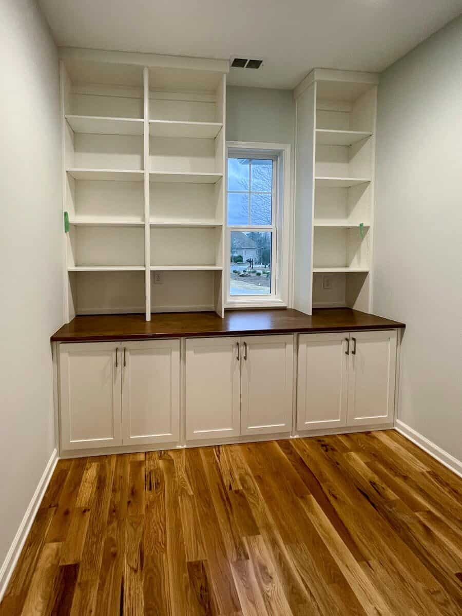 The walk-in closet has built-in shelves, white cabinets, a wooden counter, and a small glass window.