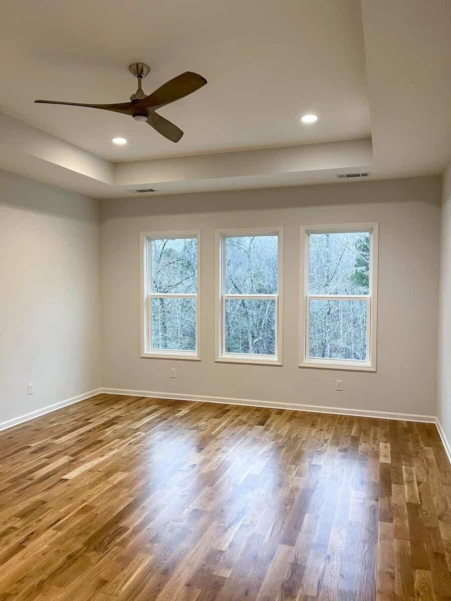 The primary bedroom features a tray ceiling, hardwood floor, and a trio of windows that invite natural light in.