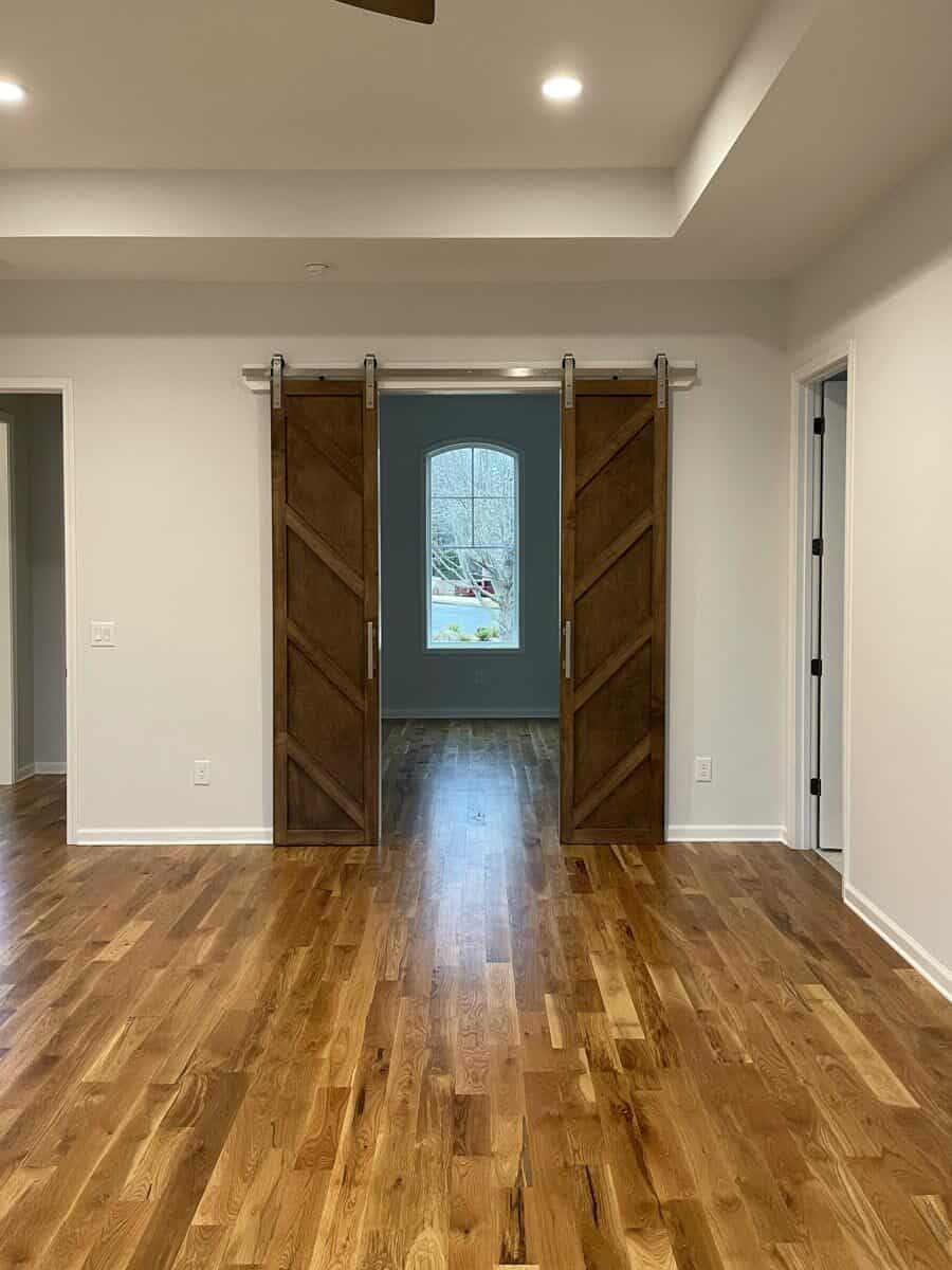 A double barn door leads to the primary walk-in closet illuminated by an arched window.