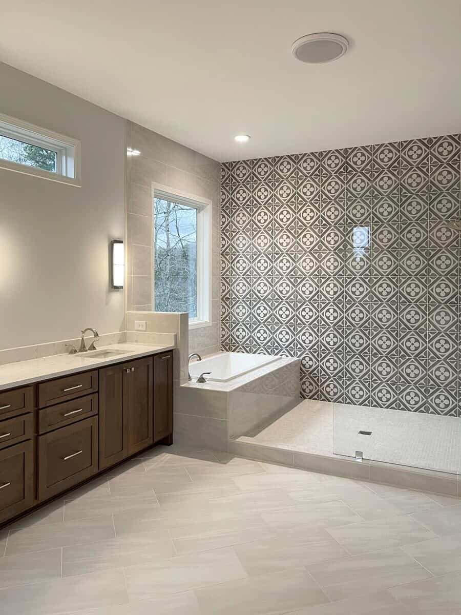 The primary bathroom is equipped with a sink vanity, drop-in tub, and walk-in shower accentuated by a decorative tile backsplash.The primary bathroom is equipped with a sink vanity, drop-in tub, and walk-in shower accentuated by a decorative tile backsplash.