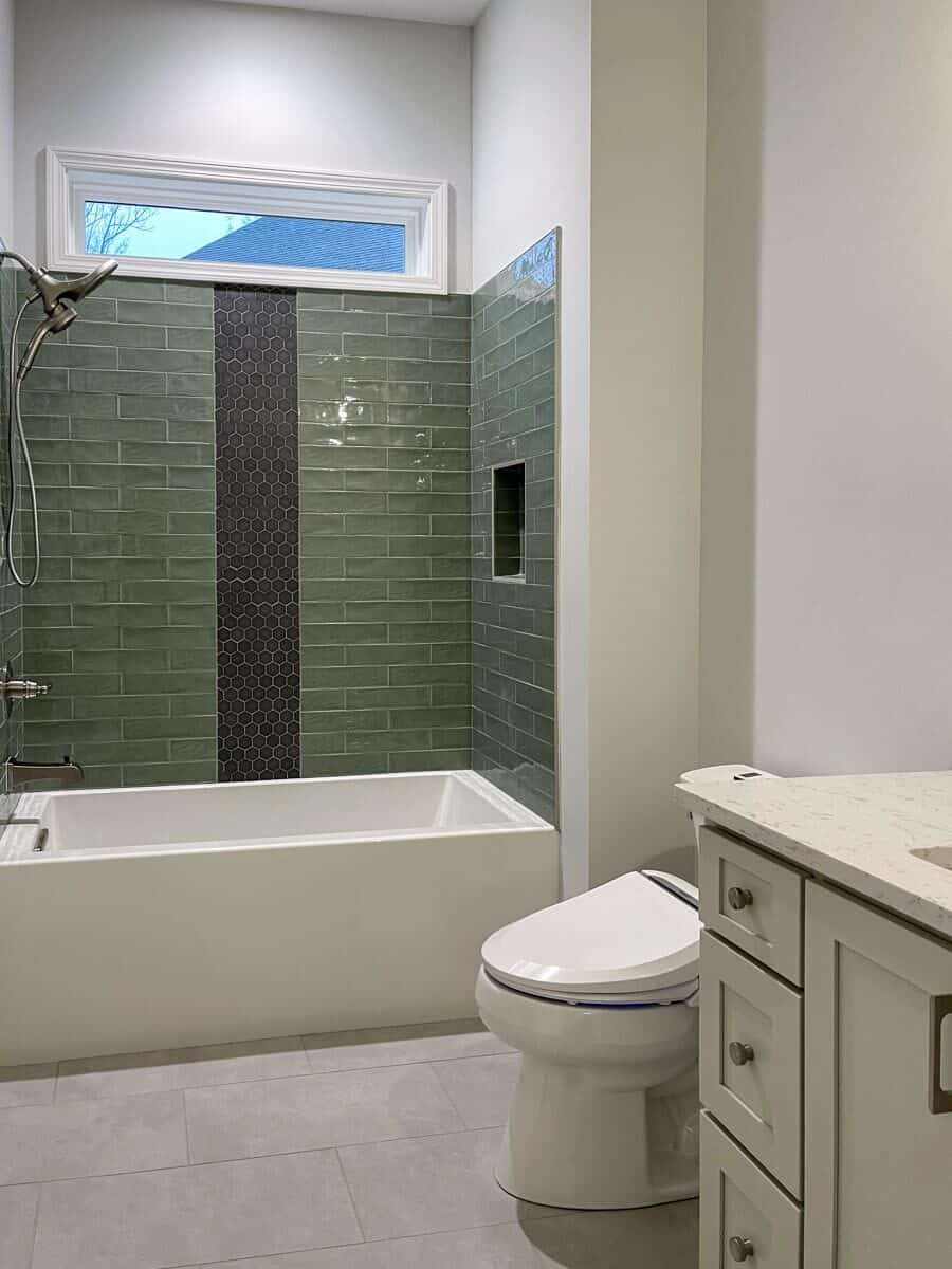 Another bathroom with a tub and shower combo, a toilet, and white vanity.