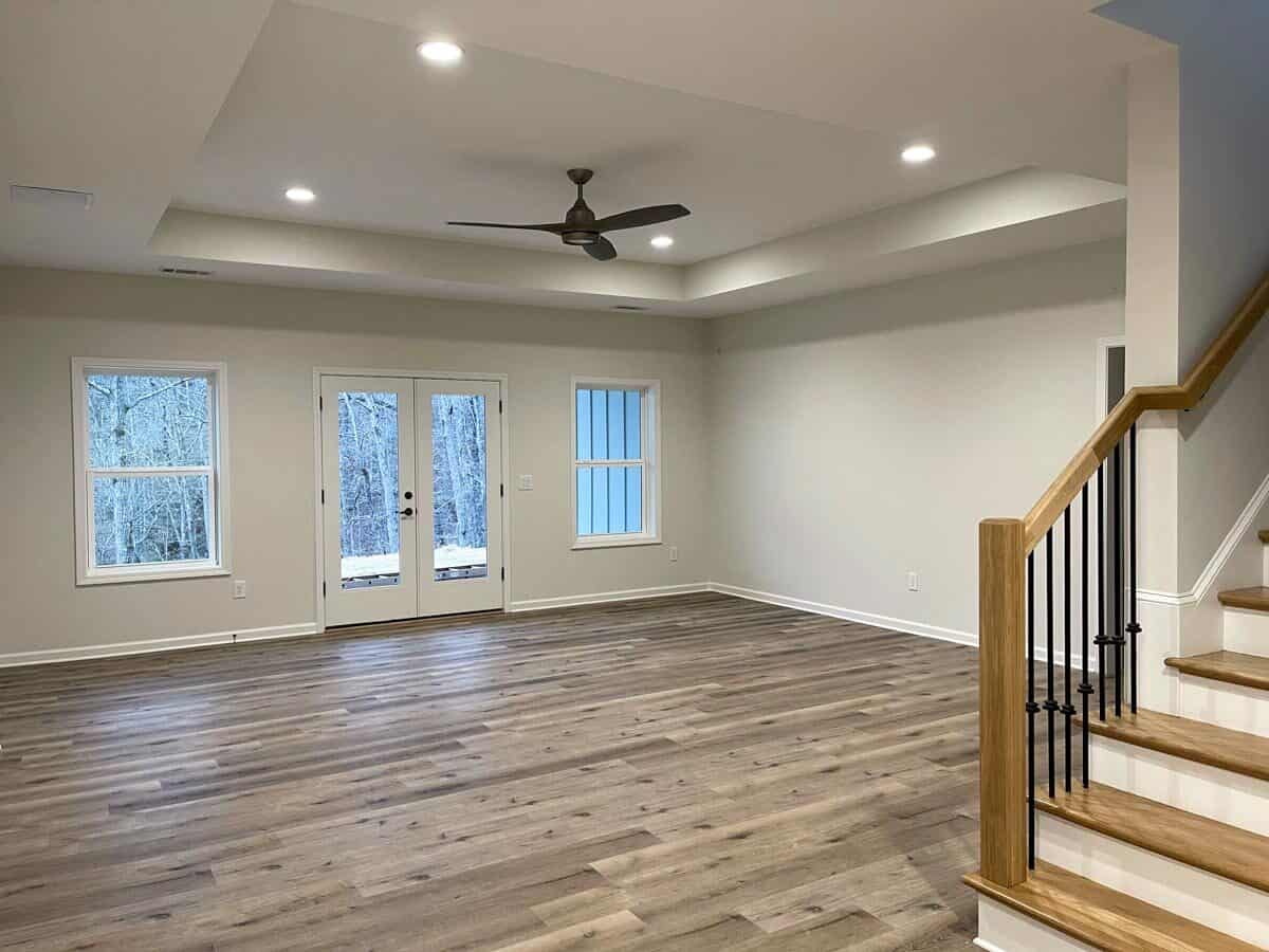 Recreation room with a tray ceiling, hardwood flooring, and a french door leading out the open patio.