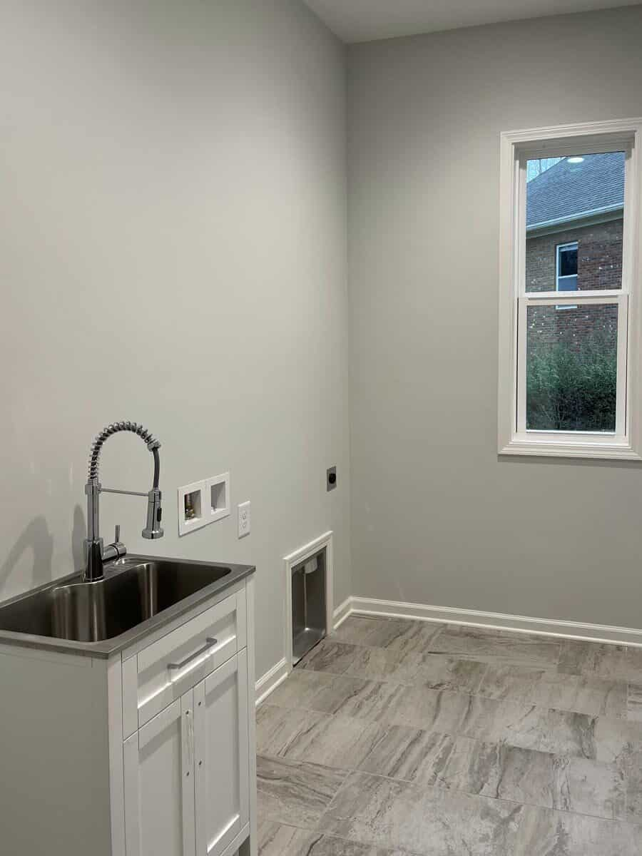 Laundry room with a utility sink over marble tiled flooring.