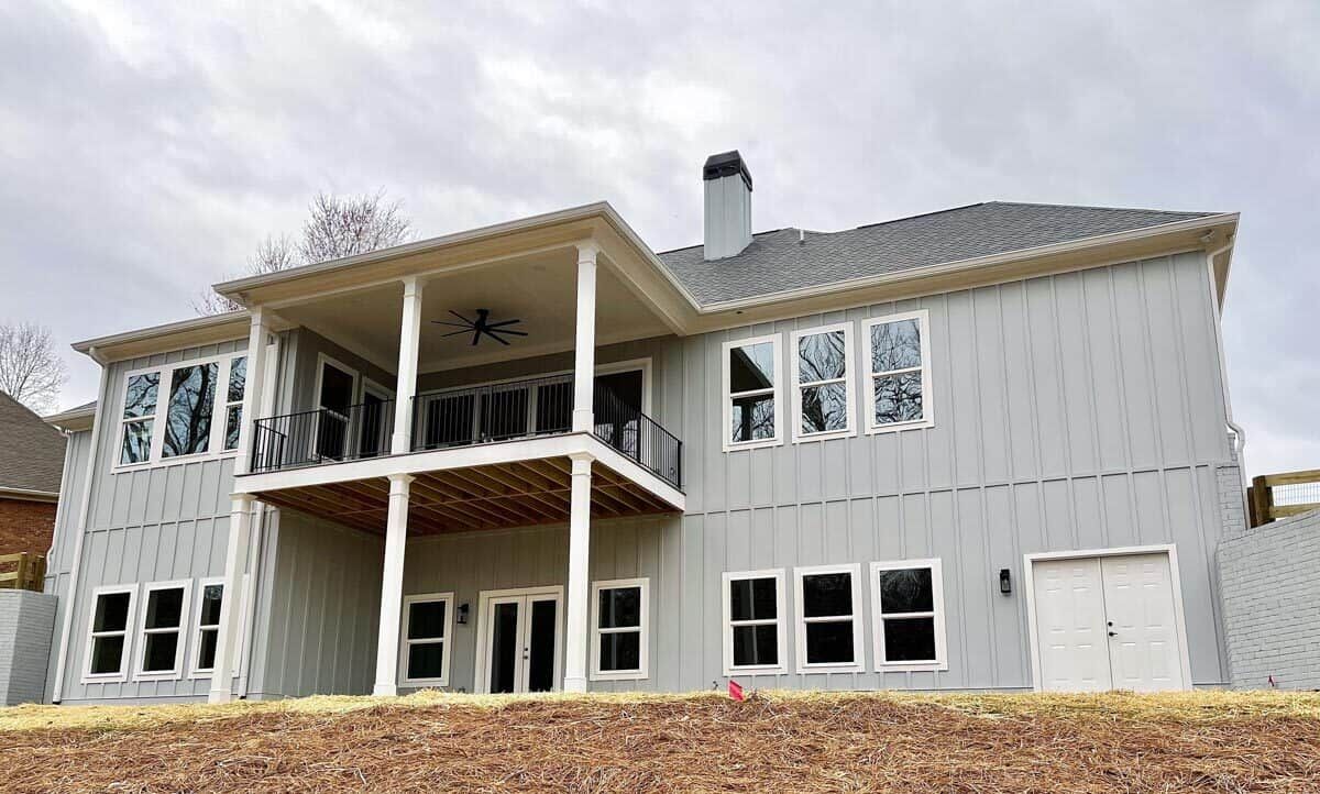 Rear exterior view showing a multitude of windows, an open patio, and a covered deck supported by white columns.