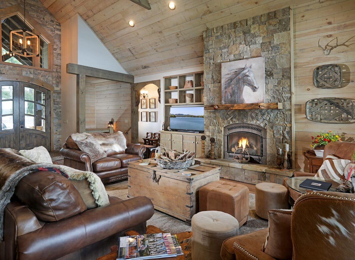 The living room has brown leather seats, a stone fireplace, and a trunk chest coffee table that matches the wood-paneled walls.