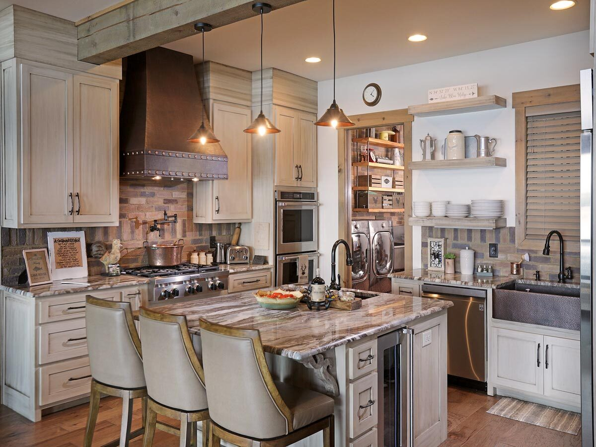 The kitchen is equipped with a farmhouse sink, light wood cabinets, stainless steel appliances, and a granite top island fitted with another sink.
