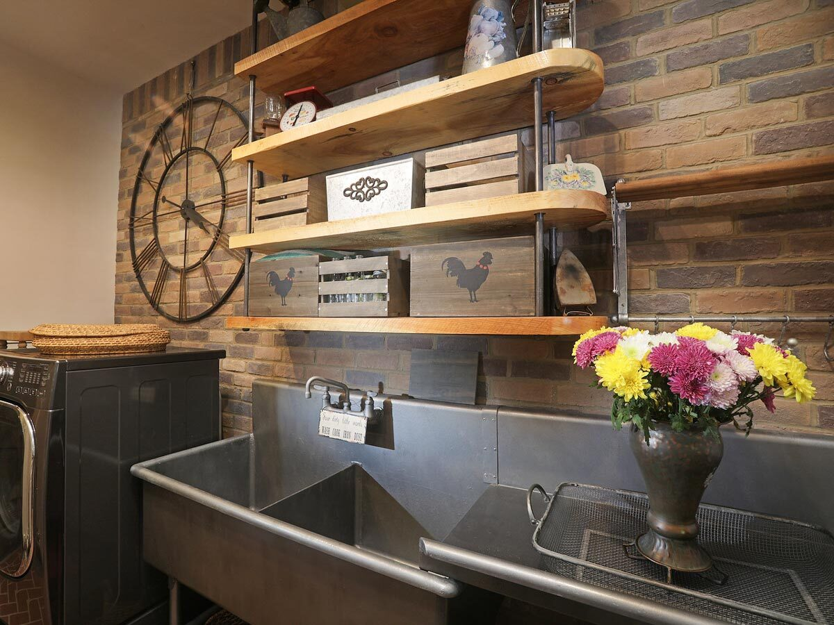Laundry room with a brick accent wall, floating shelves, front-load appliances, and a utility sink.