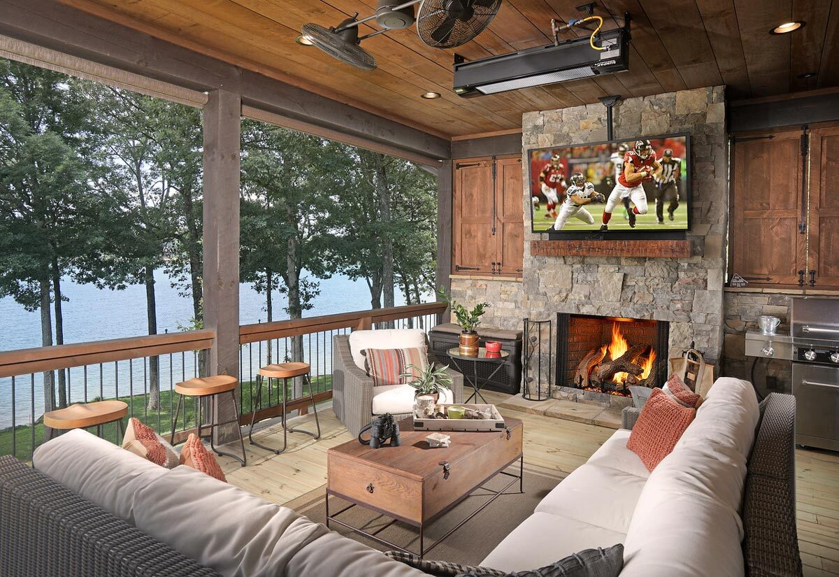The outdoor living is filled with wicker seats, round stools, a summer kitchen, and a stone fireplace topped with a TV.