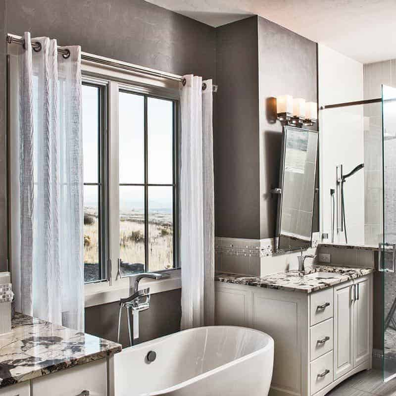 This is a close look at the primary bathroom with a couple of white vanities flanking a freestanding bathtub under a window with curtains.