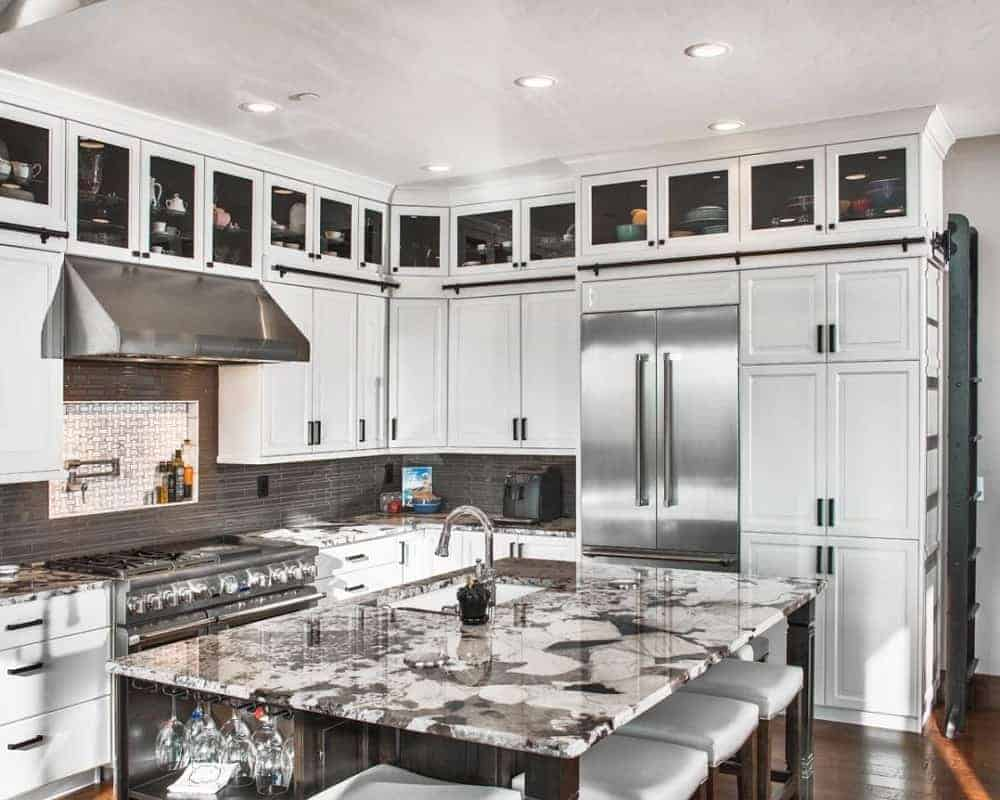 This is a close look at the large kitchen brightened by its white shaker cabinets and white ceiling that has recessed lights. These are then complemented by the dark marble counter, dark backsplash and the rows of glass panels at the top cabinet.
